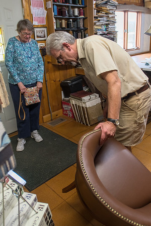 "Lenny Hiniker (right) shows Marcia Mason a chair he reupholstered for her at Hiniker's business Upholstery Service Company. ""This is just perfect, it's just gorgeous,"" said Mason when she picked up the chair. Photo by Jackson Forderer"
