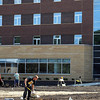 Landscapers work on installing a sprinkler system outside Minnesota State's new dormitory, Preska Hall.