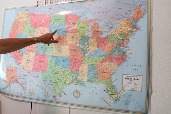 Paul Bruderlie points to one of his clients that he repaired two-way radios for in South Dakota. Bruderlie has marked his national and international clients on a map in his home office. Photo by Jackson Forderer