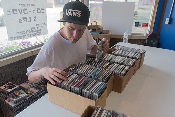 Tyler Pieper alphabetizes CDs that will be put up for sale on the website discogs.com. Pieper said online is another way for the record store to make sales. Photo by Jackson Forderer