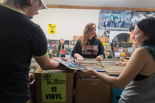 From left, Zac Ehlers, Hannah Hall and Taylah Lawton look through vinyl in the basement of Tune Town. Photo by Jackson Forderer