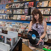 Kathy Sonnek looks at a piece of vinyl while shopping at Tune Town. Photo by Jackson Forderer