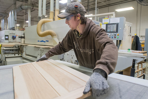 Dale Ringle picks up a cabinet door at the Elkay Wood Products plant in New Ulm. Photo by Jackson Forderer