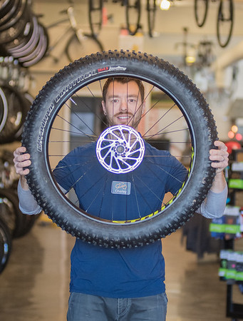 Charley Serrill, owner of Nicollet Bike Shop, holds up a fat tire in the showroom. Fat tire bikes started gaining popularity about five years ago in the bicycle world. Photo by Jackson Forderer