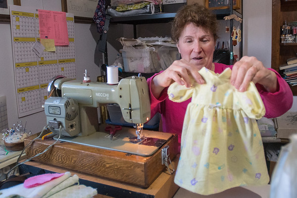 Mary Hale looks over a night gown that she made for a doll  in about 15 minutes at her home in Mankato. Hale said that she will walk through a fabric store and imagine what kind of clothes she could make from the fabric she sees. Photo by Jackson Forderer