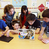 Alex Mielens, 14,  Nathan Stallings, 14,  Jack Lawlor, 14, and Ethan Calandra, 14, work in class  with Rachel Fonseca, 13, left, and Ashvi Patel, 14. The Hampstead Academy eighth graders won a design competition for their mobile app. <br /> Photo by Amy Sweeney