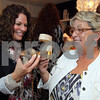 Photo by Frank J. Leone, Jr.   Admiring a designer shoe style, at left, Chris Hubbell of North Andover and Linda Edelman of Loudon,<br /> mother of co-owner Stephanie Sipley,<br /> at the One Year Anniversary of Sole Amour Shoe Apparel Store,  Thursday, in Andover.<br /> 4/26/12