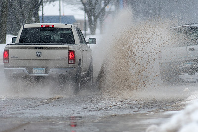 A truck splashes up a puddle of water on Belgrade in North Mankato as rain changed into snow on Saturday afternoon. Photo by Jackson Forderer