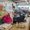 Kathy Hauser (left), a volunteer with PACT Ministries, bags up items for a customer at the Neighborhood Thrift Store. Hauser says she enjoys the people and what items come into the store. Photo by Jackson Forderer