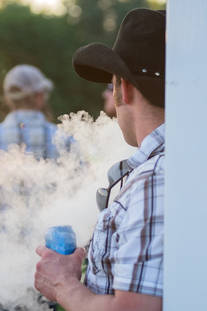 Luke Zollnar of North Mankato exhales while vaping an e-cigarette before the start of the Gary Allan concert held at Vetter Stone Amphitheater. Photo by Jackson Forderer