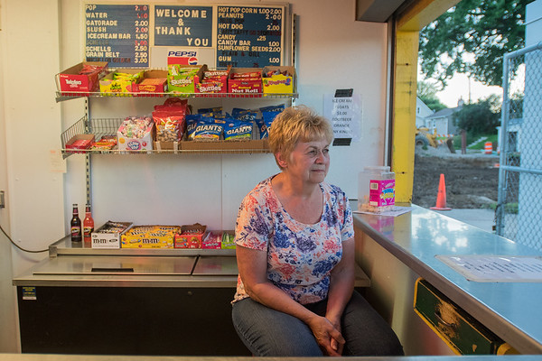 Leanna Fluegge watches the New Ulm Brewers game from the concession stand at Johnson Park. Fluegge has run the concession stand for 20 years. Photo by Jackson Forderer