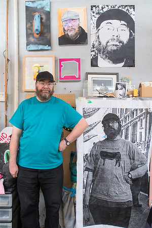 Curt Germundson mimics his stance in a previous portrait taken of him in New York City, at the 410 Project. Two other pieces of art depicting Germundson are also displayed on the wall. Photo by Jackson Forderer