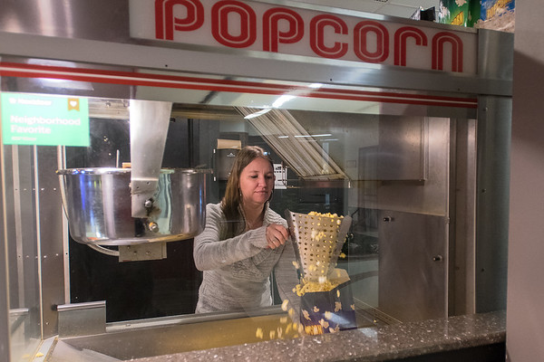 Jamie Hiniker fills a bag of popcorn at the Cine Grand 4 movie theater in downtown Mankato. The theater features cheaper ticket prices and reclining seats. Photo by Jackson Forderer