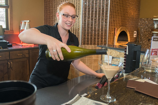 Laura Sease pours a glass of Valnot, a creme liquor, made by Chankaska Winery for a customer at their tasting room in Kasota. Photo by Jackson Forderer
