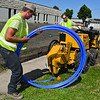 Two Green Care employees install a sprinkler system in front of Paragon Printing. Green Care was voted as the best lawn care company. Photo by Jackson Forderer