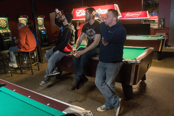 From left, Trevor Hustad, Darren Pettersen and Jacob Gieser watch the band Bobaflex from the pool tables at Red Rocks. Photo by Jackson Forderer