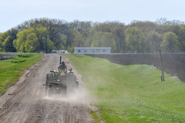 Andy Duffey drives his tractor down a gravel road with a four-wheeler in tow in rural Judson as the planting season was in full swing. A stretch of warm, dry weather gave area farmers a window just large enough to get all of their crops in the soil. Photo by Jackson Forderer