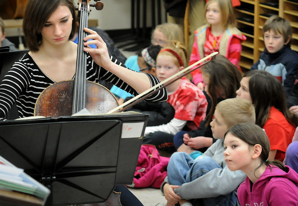 John Cross<br /> Area third-graders watch West High School cellist Amy Poburka and other strings section musians demonstrate their intstruments.