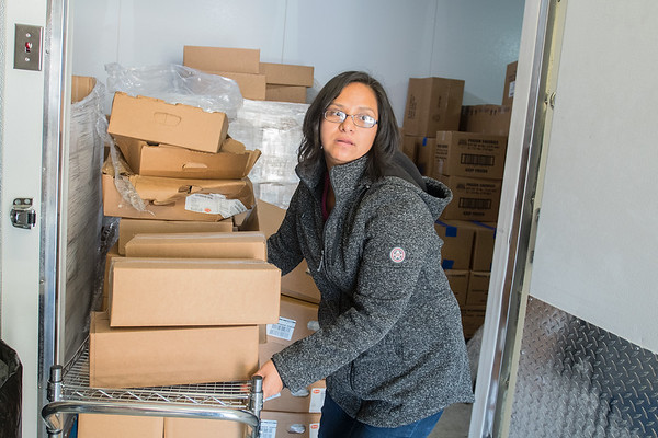 Deisy De Leon Esqueda gets boxes of food out of a freezer at the ECHO Food Shelf in September. De Leon Esqueda has been the manager at the food shelf since 2003. Photo by Jackson Forderer