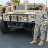 """Freda Steffl, originally from Nigeria, joined the Army and is still in the Army Reserve. She is pictured here in front of a humvee at the Mankato Armory. Steffl said one of the reasons she joined the Army was because of its rigorous physical training. """"I'm so obsessed with being strong,"""" she added. Photo by Jackson Forderer"""