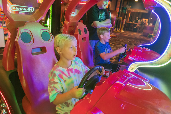 Andrew Carson (left), 8, and Abe Carson, 10 play a racing game in the arcade at the Wow! Zone. Photo by Jackson Forderer