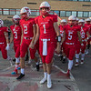 The Mankato West football team, led by quarterback Jack Foster (1), walks to the football field for their season opening game against Rochester John Marshall.