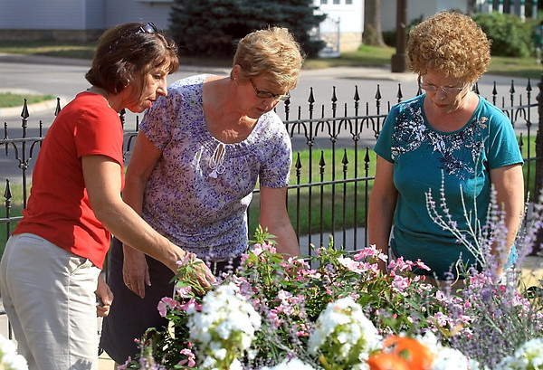 From left, Shirley Hoelscher, Bonnie Sellner and Marily Lerud look at the flowers in the garden near the R.D. Hubbard House Tuesday. The trio are members of the Twilight Garden Club that gathers at the park on Tuesdays to tend the garden.