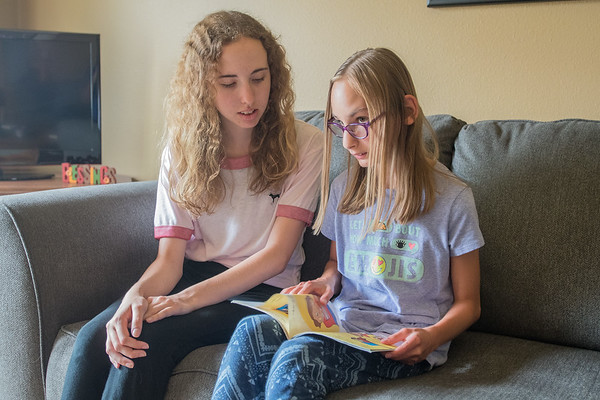 Grace Schwertfeger (right), 12, reads to her sister Autumn, 14, at their house in Mankato. Grace was born 16 weeks prematurely and has trouble reading because of problems with her eyesight. Photo by Jackson Forderer
