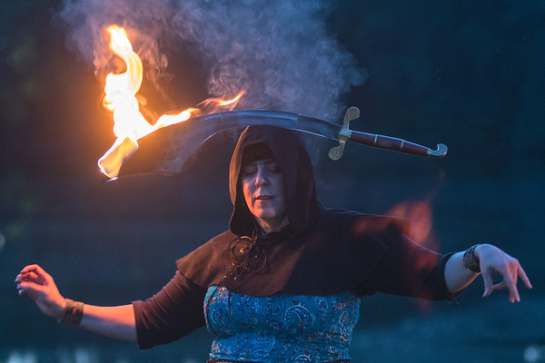 Patrice Hundstad balances a sword on her head while dancing with the group Wóȟpe Fire Bellydance at Hiniker Pond. Photo by Jackson Forderer