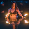 Jess Hansen-Barnett of the Wóȟpe Fire Bellydancers with palm torches in Hiniker Pond. Photo by Jackson Forderer