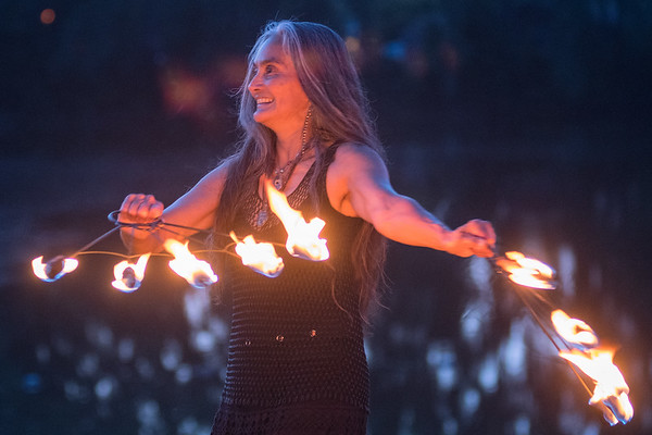 Elaine Hardwick with Wóȟpe Fire Bellydance dances with fans of fire during a group practice at Hiniker Pond. Photo by Jackson Forderer