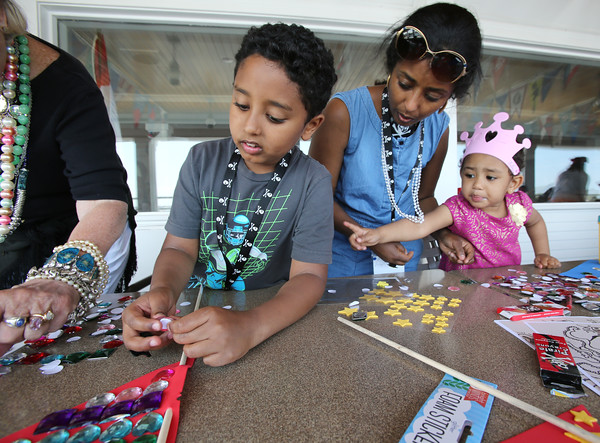 KEN YUSZKUS/Staff photo.   Henok Gebreselassie, 8, left, creates a pennant. His mother Frey Teklewold and sister Mare Gebreselassie, 3, of Medford, help out while attending the Sailing Heals Pirates and Princesses Treasure Hunt Adventure held at the Boston Yacht Club in Marblehead.     06/29/16