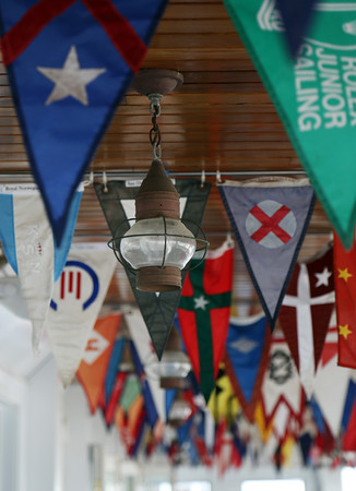 DAVID LE/Staff photo. Flags from yacht clubs around the world accent the ceiling of the outdoor dining area at the Boston Yacht Club.