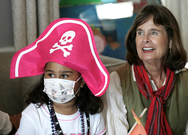 """KEN YUSZKUS/Staff photo.  Marina Abad, 9, of East Boston, and Marblehead """"captain"""" Libby Moore watch The Comedy Magic of Dondo at the Sailing Heals Pirates and Princesses Treasure Hunt Adventure held at the Boston Yacht Club in Marblehead.     06/29/16"""