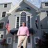 DAVID LE/Staff photo. Boston Yacht Club Commodore Barry Klickstein stands outside the front doors of the club on Front Street in Marblehead.