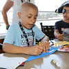 KEN YUSZKUS/Staff photo.   Zayd Benayoud, 7, left, and his brother Bilal, 7, of North Andover, create pennants at the Sailing Heals Pirates and Princesses Treasure Hunt Adventure held at the Boston Yacht Club in Marblehead.     06/29/16