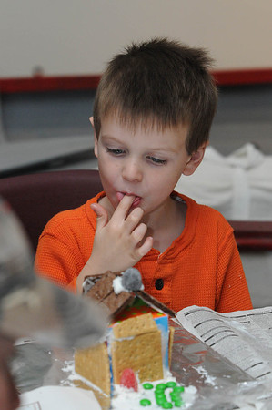 Marblehead:<br /> Jake Lemieux, 4, tastes the frosting used in the building of a gingerbread house during the gingerbread house workshop at the Marblehead Museum. One of two workshops which are part of the Marblehead Christmas Walk. <br /> Photo by Ken Yuszkus/Salem News, Tuesday, November 29, 2011.