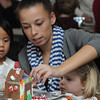 Marblehead:<br /> From left, Cornelia Payne, 4, gets help from her babysitter, Avril Williams, as sister, Eliza Payne, 3, watches the construction of a gingerbread house during the gingerbread house workshop at the Marblehead Museum. One of two workshops which are part of the Marblehead Christmas Walk. <br /> Photo by Ken Yuszkus/Salem News, Tuesday, November 29, 2011.