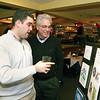 Marblehead:Ê Artist Steve N. Bruno, at left, shows his dad, Steve A. Bruno his logo which finished in the final four, both are from Marblehead, at the Marblehead Festival of Arts Annual Logo Premiere Party, Tuesday, at the Landing Restaurant, Marblehead.Ê Photo by Frank J. Leone, Jr.<br /> ÊÊÊÊÊÊÊÊÊÊÊÊÊÊÊÊÊÊÊÊÊÊÊÊÊ