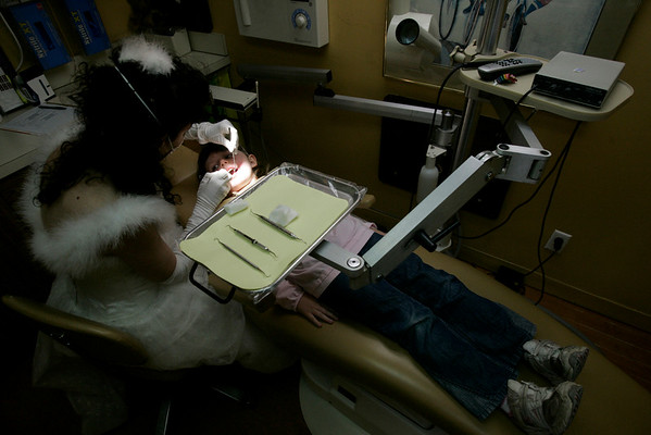 Dr. Corine Barone, a pediatric dentist who dresses up as the tooth fairy, examines Gwen Sullivan, 5, of Marblehead.