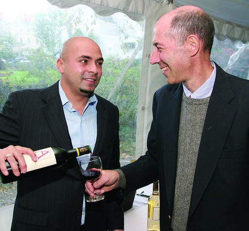 Marblehead:Ê At left, Isaac Perez of Pasternak Wine Imports, Boston, pours a glass of vintage French cabernet wineÊto George Shubie, co-host of the evening and proprietor of Shubie's, he is from Marblehead, at Shubie's Harvest Wine & Food Festival to benefit the Friends of Marblehead Public Schools and the Marblehead Museum and Historical Society, Friday, at the Jeremiah Lee Mansion, Marblehead. Photo by Frank J. Leone, Jr.