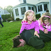 Julia Kellog, 5, left, helps her twin sister, Phoebe, 5, pin their father, Jaime Kellog, as their mother, Kate, and brother, Jay, 7, watch them wrestle in the Kellog's backyard on Longfellow Road in the Goldthwait Beach neighborhood in Marblehead.