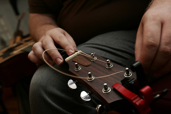 Ethan Scott Baird of the band Pesky J. Nixon strings his guitar before the start of the last Me and Thee Coffeehouse of the season held at the Unitarian Universalist Church in Marblehead. Photo by Deborah Parker/August 5, 2009