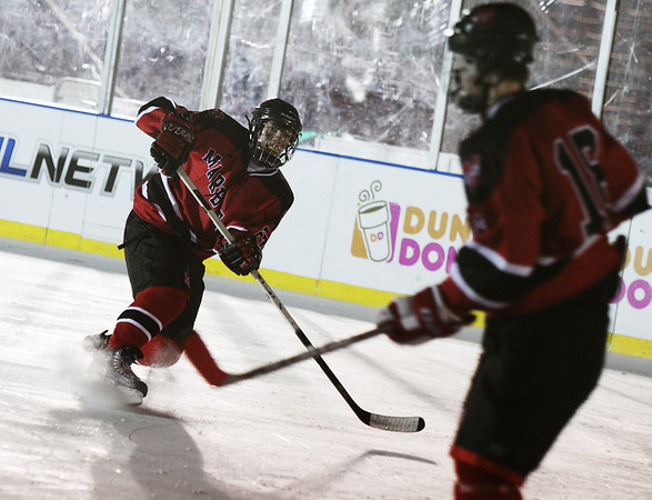 Boston: Hunter Whitmore sends the puck down the ice during Marblehead's game against Winthrop at Fenway Park Saturday night.  Photo by Liz Curtis
