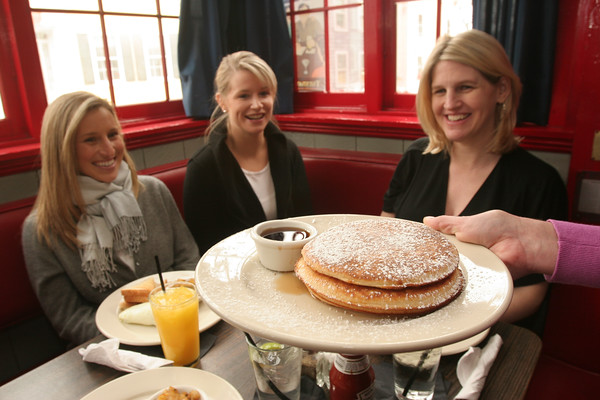 Marblehead: A plate of pancakes arrives as, from left to right, Natalie Katz and Cheryl Wadsworth from Boston, and Sarah O'Toole from Marblehead enjoy drinks in a corner table at Maddie's Sail Loft in Marblehead as they during Sunday brunch. Photo by Matthew Viglianti/Staff Photographer Sunday, January 24, 2010.