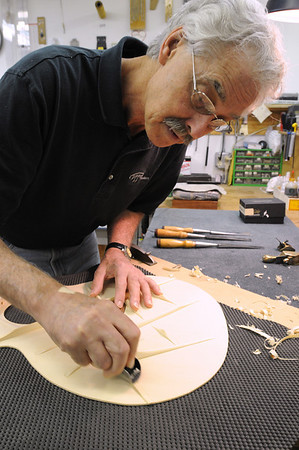 Marblehead:<br /> Bill Tippin is voicing the guitar top by shaving small amounts. Bill Tippin makes guitars in his shop.<br /> Photo by Ken Yuszkus/Salem News, Friday, July 10, 2009.