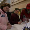 Marblehead: Mary Orne fills out raffle tickets with her son, Harry, 11, and Harry's grandfather, Raymond, right, as her husband, Gerry watches at the 2009 Marblehead Home and Garden Show at the Marblehead Community Center. Photo by Matthew Viglianti/Staff Photographer March 22, 2009.