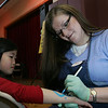 Marblehead: Mei Humenn, 8, of Marblehead has her arm decorated by Claire Dumond at the 2009 Marblehead Home and Garden Show at the Marblehead Community Center. Photo by Matthew Viglianti/Staff Photographer March 22, 2009.