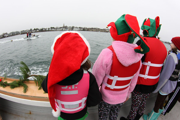Marblehead: Santa and Mrs. Claus arrive at State Street in Marblehead from a lobster boat hailing from the North Pole as throngs of children gather to greet them.  A few lucky children dressed as elves got to accompany Santa on the boat.  Photo by Liz Curtis