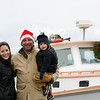 Marblehead: Santa and Mrs. Claus arrive at State Street in Marblehead from a lobster boat hailing from the North Pole as throngs of children gather to greet them.  Captaining the boat was Jay Sahagian, seen here with wife Rebecca and son Carter.  Photo by Liz Curtis